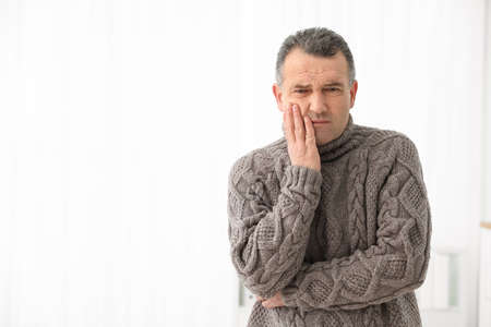 Photo for Mature man suffering from strong tooth pain on light background, space for text - Royalty Free Image