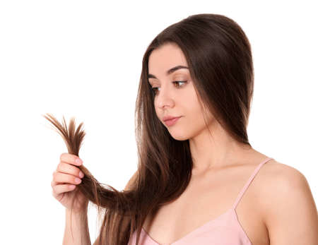 Photo pour Emotional woman with damaged hair on white background. Split ends - image libre de droit