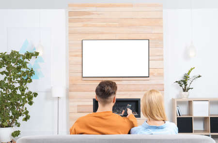 Photo pour Couple watching TV on sofa in living room with decorative fireplace - image libre de droit