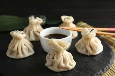 Foto de Slate plate with tasty baozi dumplings, chopsticks and soy sauce on table - Imagen libre de derechos