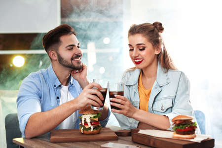 Photo pour Happy young couple having lunch in burger restaurant - image libre de droit