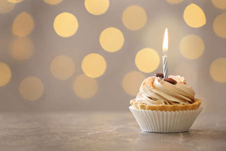 Photo for Tasty birthday cupcake with candle on table against blurred lights, space for text - Royalty Free Image