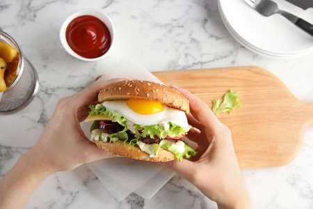 Photo for Woman holding tasty burger with fried egg over table, top view - Royalty Free Image