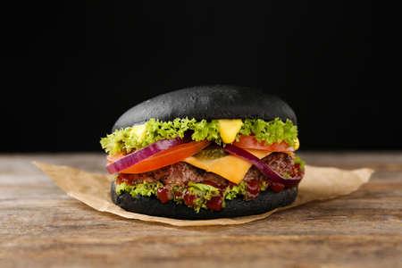 Photo pour Tasty black burger on table against dark background - image libre de droit