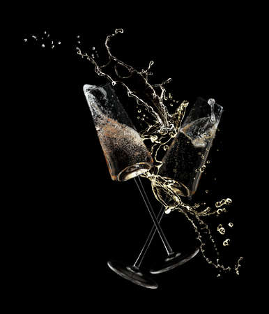 Foto de Glasses of champagne clinking together and splashing on black background - Imagen libre de derechos