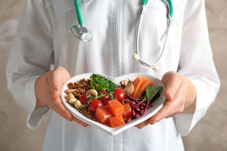 Foto de Doctor holding plate with products for heart-healthy diet, closeup - Imagen libre de derechos