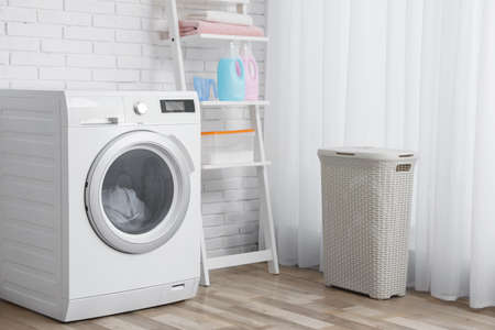 Photo pour Modern washing machine near brick wall in laundry room interior - image libre de droit