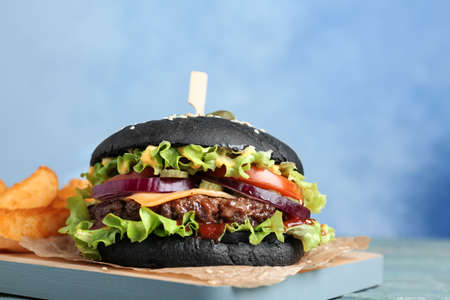 Photo pour Board with black burger and french fries on table, closeup. Space for text - image libre de droit