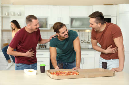Photo for Group of friends with tasty food laughing together in kitchen - Royalty Free Image