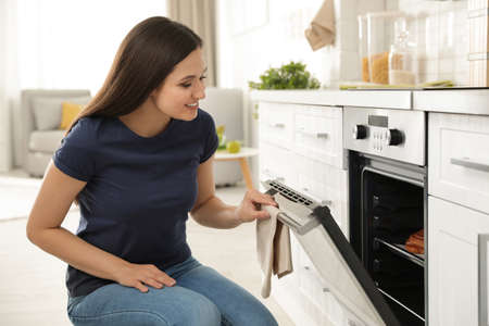 Photo pour Beautiful woman opening door of oven with baked buns in kitchen - image libre de droit