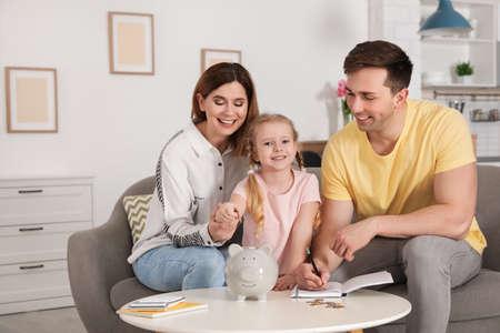 Photo pour Happy family putting coin into piggy bank at table indoors. Saving money - image libre de droit
