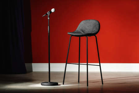 Photo pour Microphone and stool on stage against color wall - image libre de droit