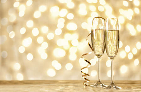 Photo for Glasses of champagne on table against blurred lights. Space for text - Royalty Free Image
