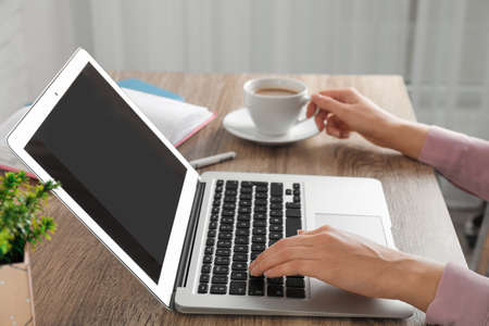 Foto de Woman using laptop at table, closeup. Space for design - Imagen libre de derechos