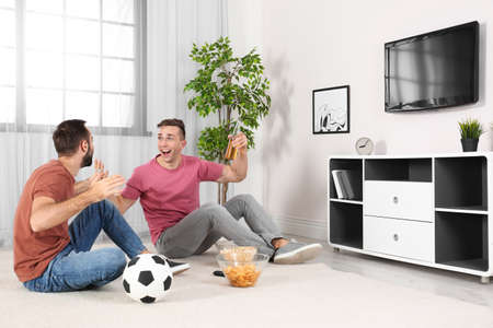 Photo pour Young men watching TV while sitting on floor at home. Sport channel - image libre de droit