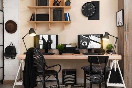 Foto de Stylish workplace interior with computers on table - Imagen libre de derechos