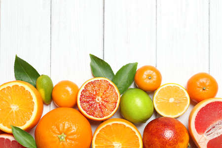 Photo for Flat lay composition with different citrus fruits and space for text on white wooden background - Royalty Free Image