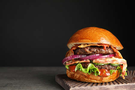 Photo for Tasty burger with bacon on table against black background. Space for text - Royalty Free Image