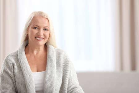 Photo pour Portrait of beautiful older woman against blurred background with space for text - image libre de droit