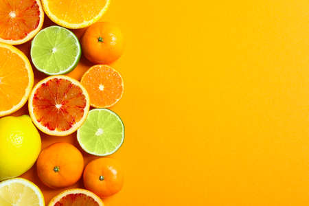 Photo for Different citrus fruits on color background, flat lay. Space for text - Royalty Free Image