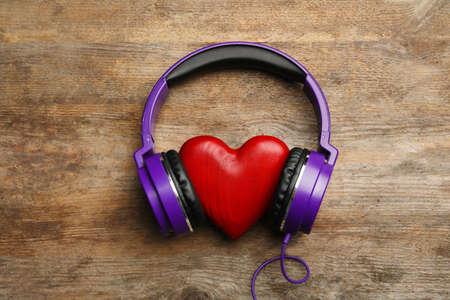 Foto de Decorative heart with modern headphones on wooden background, top view - Imagen libre de derechos