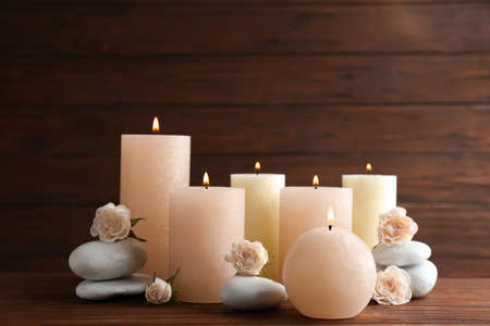 Photo pour Composition of burning candles, spa stones and flowers on table. Space for text - image libre de droit