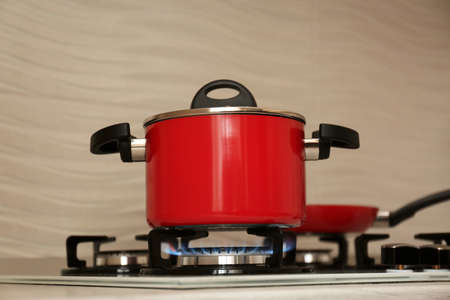 Photo pour Red pot and frying pan on modern gas stove - image libre de droit