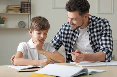Photo for Dad helping his son with school assignment at home - Royalty Free Image