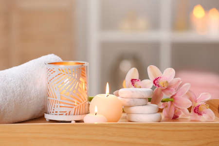 Photo pour Composition with candles, flowers and stones on wooden table in spa salon. Space for text - image libre de droit