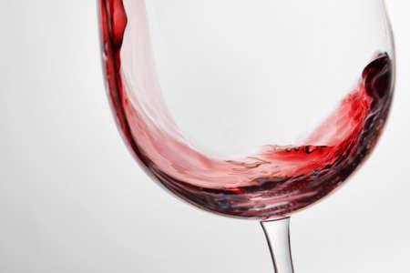 Photo pour Pouring red wine into glass on light background, closeup - image libre de droit
