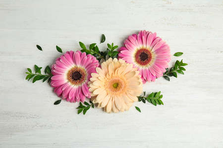 Photo for Flat lay composition with beautiful bright gerbera flowers on wooden background - Royalty Free Image