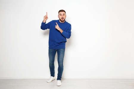 Photo pour Full length portrait of emotional man against white wall. Space for text - image libre de droit
