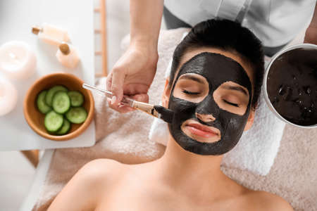 Photo for Cosmetologist applying black mask onto woman's face in spa salon, top view - Royalty Free Image