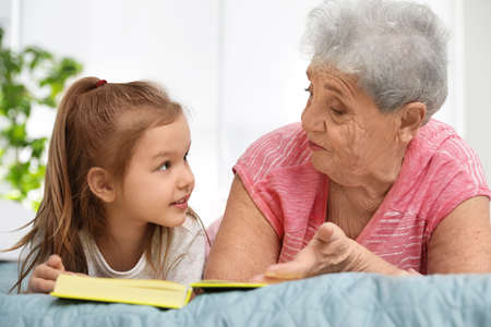 Photo pour Cute girl and her grandmother reading book on bed at home - image libre de droit