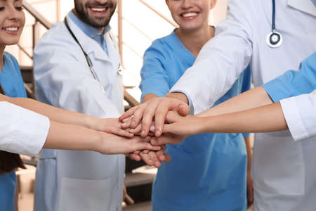 Foto de Team of medical doctors putting hands together indoors, closeup. Unity concept - Imagen libre de derechos