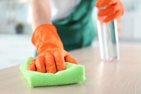 Photo for Worker in gloves cleaning table with rag, closeup. Space for text - Royalty Free Image
