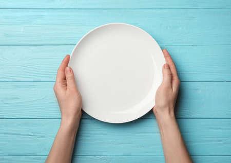 Photo pour Woman with empty plate at wooden table, top view - image libre de droit
