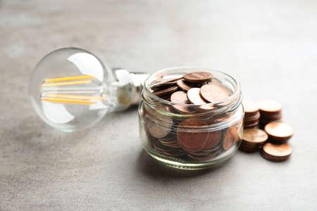 Photo pour Glass jar, coins and light bulb on grey background - image libre de droit