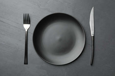 Photo pour Stylish ceramic plate and cutlery on dark background, flat lay - image libre de droit