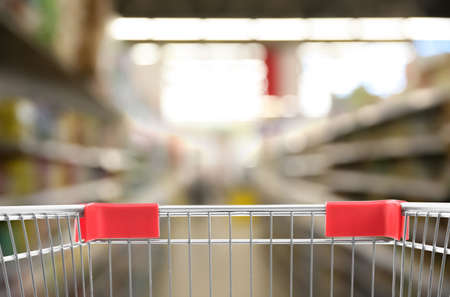 Blurred view of supermarket and empty shopping basket, closeup