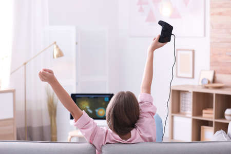 Photo for Emotional young woman playing video games at home - Royalty Free Image