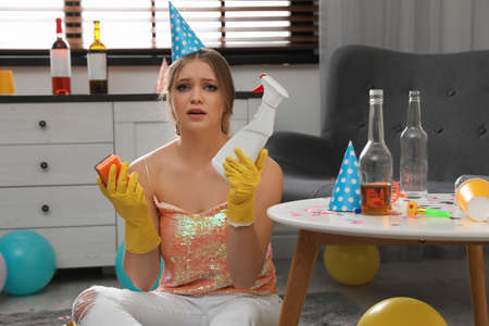 Tired young woman with bottle of detergent and sponge in messy room after party