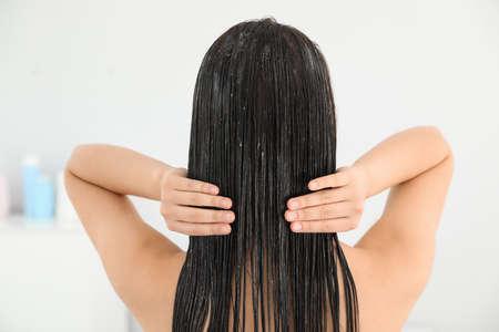 Photo pour Woman applying hair conditioner in light bathroom - image libre de droit