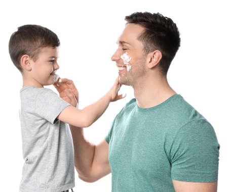 Photo pour Dad and his little son applying shaving foam against white background - image libre de droit