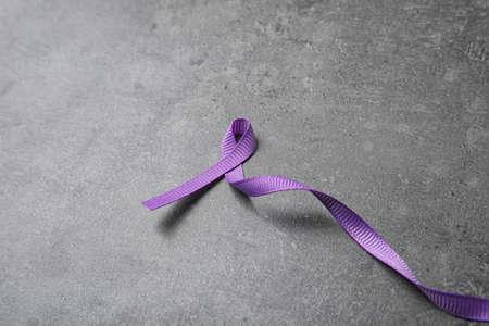 Foto de Purple ribbon on grey stone background, space for text. Domestic violence awareness - Imagen libre de derechos