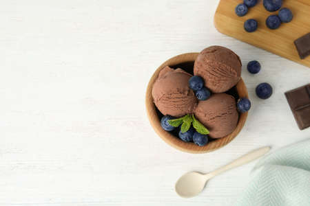 Flat lay composition with bowl of chocolate ice cream and blueberries on white wooden table, space for text