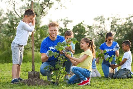 Photo pour Kids planting trees with volunteers in park - image libre de droit