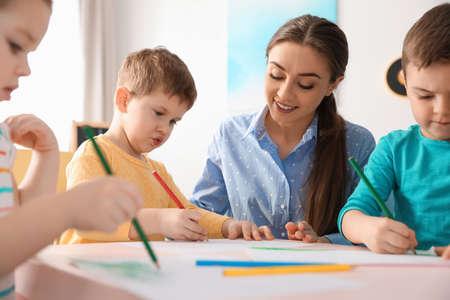 Foto de Little children with kindergarten teacher drawing at table indoors. Learning and playing - Imagen libre de derechos