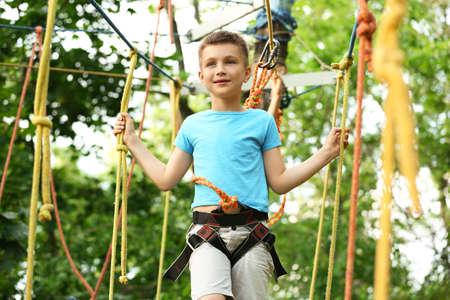 Photo pour Little boy climbing in adventure park. Summer camp - image libre de droit