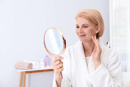 Photo for Mature woman with mirror applying face cream at home - Royalty Free Image
